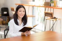 Mooi van portret bedrijfs Aziatische jonge vrouwenlezing op notitieboekje met succes op lijst Stock Foto