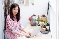 Mooi van portret het Aziatische jonge vrouw werken online aan laptop zitting bij koffiewinkel Royalty-vrije Stock Afbeeldingen