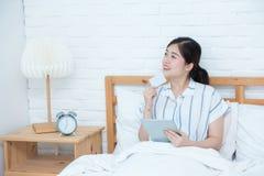 Mooi van zitting van de portret de jonge Aziatische vrouw denk gebruikscreditcard met tablet, Tevreden meisje online en betaling  royalty-vrije stock afbeeldingen