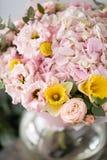 Mooi vers besnoeiingsboeket van gemengde bloemen in vaas op houten lijst het werk van de bloemist bij een bloemwinkel gevoelig stock fotografie
