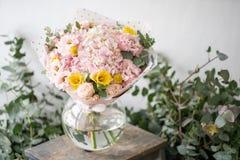 Mooi vers besnoeiingsboeket van gemengde bloemen in vaas op houten lijst het werk van de bloemist bij een bloemwinkel gevoelig stock afbeeldingen