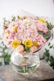 Mooi vers besnoeiingsboeket van gemengde bloemen in vaas op houten lijst het werk van de bloemist bij een bloemwinkel gevoelig stock foto's