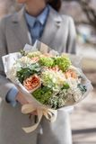 Mooi vers besnoeiingsboeket van gemengde bloemen in vrouwenhand het werk van de bloemist bij een bloemwinkel Gevoelige pastelkleu stock afbeelding