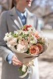 Mooi vers besnoeiingsboeket van gemengde bloemen in vrouwenhand het werk van de bloemist bij een bloemwinkel Gevoelige pastelkleu stock foto