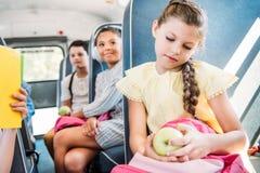 mooi vervoeren weinig schoolmeisje met rugzak en appel die op school berijden met vage klasgenoten per bus stock afbeeldingen