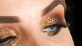 Mooi vet vrouwenmodel met gouden make-up, de rokerige valse wimpers van de ogen donkerrode lippenstift en blauwe ogen die op een  stock videobeelden