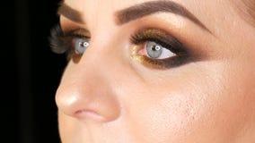 Mooi vet vrouwenmodel met gouden make-up, de rokerige valse wimpers van de ogen donkerrode lippenstift en blauwe ogen die op een  stock video