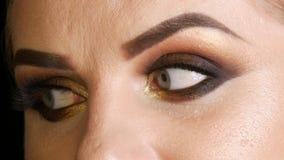 Mooi vet vrouwenmodel met gouden make-up, de rokerige valse wimpers van de ogen donkerrode lippenstift en blauwe ogen die op een  stock footage