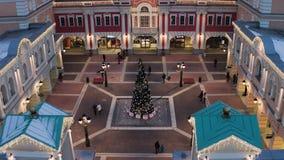 Mooi vierkant met de winter verfraaide pijnboom-boom en verlichte gebouwen stock footage