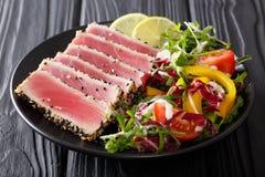 Mooi voedsel: lapje vleestonijn in dichte sesam, kalk en verse salade Stock Afbeeldingen