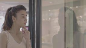 Mooi volwassen meisje die aan showcase van opslag kijken stock footage