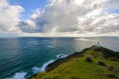 Mooi Vreedzaam Oceaanlandschap met vuurtoren op de bovenkant van klippenpiek, het lichte huis van Kaapreinga, Northland, Nieuw Ze royalty-vrije stock afbeelding