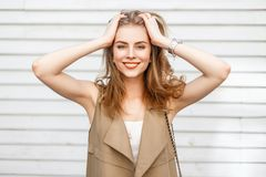 Mooi vrolijk meisje die en dichtbij een houten muur glimlachen genieten van stock afbeelding