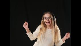 Mooi vrolijk meisje in hoofdtelefoons op zwarte achtergrond stock footage