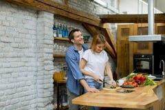 Mooi vrolijk paar kokend diner samen en hebbend pret bij rustieke keuken stock afbeeldingen