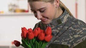 Mooi vrouw militair eenvormig het snuiven tulpenboeket, veteranendag, patriottisme stock videobeelden