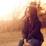 Mooi vrouwelijk model bij zonsondergang. Het dragen van zonnebril. Openluchtpo stock foto