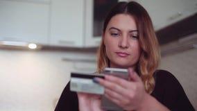 Mooi vrouwen online bankwezen die smartphone gebruiken die online met creditcard thuis levensstijl winkelen Het meisje koopt stock videobeelden
