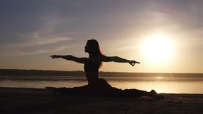 Mooi vrouwen` s silhouet die die yoga doen, op van de overzeese de zonsopgang kustochtend, smogzon op theecoulisse wordt verdeeld stock videobeelden