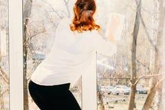 Mooi vrouwen schoonmakend venster thuis stock foto