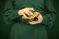 Mooi vrouwencijfer die in donkergroene 50 ` s kleding uitstekend boek houden stock foto's