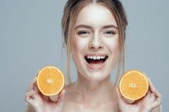 Mooi vrouwengezicht met sappige sinaasappel op grijze achtergrond Natuurlijke schoonheid en kuuroord stock afbeeldingen