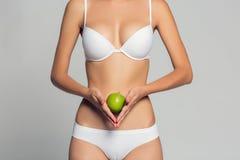 Mooi vrouwenlichaam en groene appel Conceptueel beeld van het op dieet zijn gezonde levensstijl stock fotografie