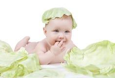 Mooi weinig baby op een witte achtergrond met groene kool stock afbeelding