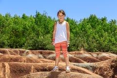 Mooi weinig blij glimlachend meisje die zich tegen de achtergrond van Cheltenham Badlands op zonnige warme dag bevinden Royalty-vrije Stock Foto's