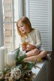Mooi weinig blond meisje die met blauwe ogen op het venster zitten Stock Foto's