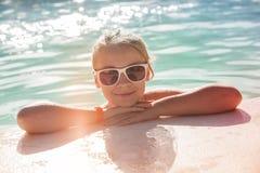 Mooi weinig blond meisje met zonnebril stock afbeelding