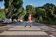 Mooi weinig gelukkig meisje die door de stad-park weg in de warme sunshiny de zomerdag rollerblading stock fotografie