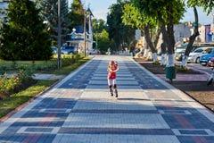 Mooi weinig gelukkig meisje die door de stad-park weg in de warme sunshiny de zomerdag rollerblading stock foto