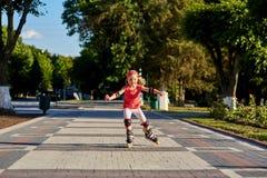 Mooi weinig gelukkig meisje die door de stad-park weg in de warme sunshiny de zomerdag rollerblading stock afbeeldingen