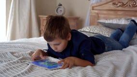 Mooi weinig jongen die op de spelen van de tabletcomputer speelt stock footage