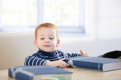 Mooi weinig jongenszitting bij lijst met boeken stock foto's