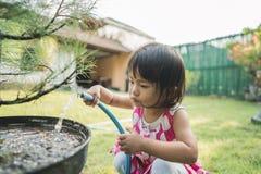 Mooi weinig kind die de installaties water geven stock foto