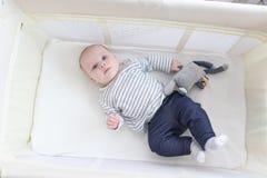Mooi weinig 3 maanden meisjes met stuk speelgoed die in reisvoederbak liggen Stock Fotografie