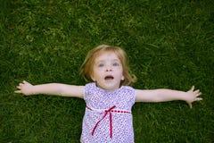 Mooi weinig peutermeisje het gelukkige liggen op gras stock foto
