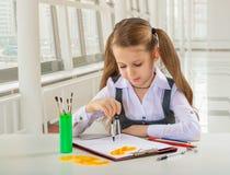 Mooi weinig schoolmeisje die bij lijst siiting stock foto's