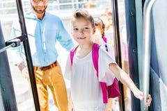mooi weinig schoolmeisje die schoolbus met leraar en klasgenoten ingaan stock fotografie