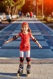 Mooi weinig sportief meisje die in de rollen in het stadspark schaatsen in zomer Stock Foto