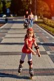 Mooi weinig sportief meisje die in de rollen in het stadspark schaatsen in zomer Royalty-vrije Stock Fotografie