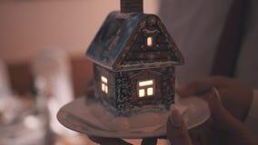 Mooi weinig stuk speelgoed huis met een binnen kaars De minnaars houden het in hun handen op een schotel Sluit omhoog stock footage