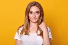 Mooi wijfje met eerlijk haar, geklede toevallige witte t-shirt, die met ernstige gelaatsuitdrukking die camera bekijken, worden g stock afbeelding