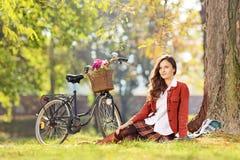 Mooi wijfje met fietszitting in een park en het bekijken c Stock Afbeeldingen