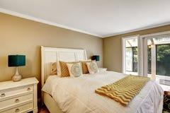 Mooi wit bed met licht toonbeddegoed en oranje details royalty-vrije stock fotografie