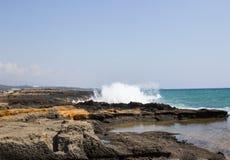 Mooi zeegezicht met golven die tegen rotsen verpletteren stock foto