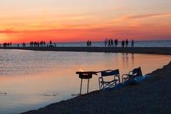 Mooi zeegezicht met mensen die op de zonsondergang letten over het overzees Stock Fotografie