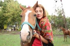 Mooi zigeunermeisje in heldere kleren met een paard en haar veulen op een landbouwbedrijf stock afbeelding